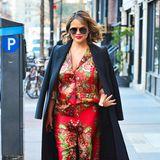 Chrissy Teigen findet in ihren Schwangerschaftslooks immer wieder schöne Kontraste, wie hier der blumige Seidenanzug in Kombination mit schlicht elegantem Mantel.
