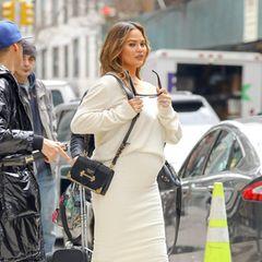Unter dem schwarzen Mantel trägt die hochschwangere Chrissy hellbraune Lederstiefel zum kuscheligen und enganliegenden Wollkleid.