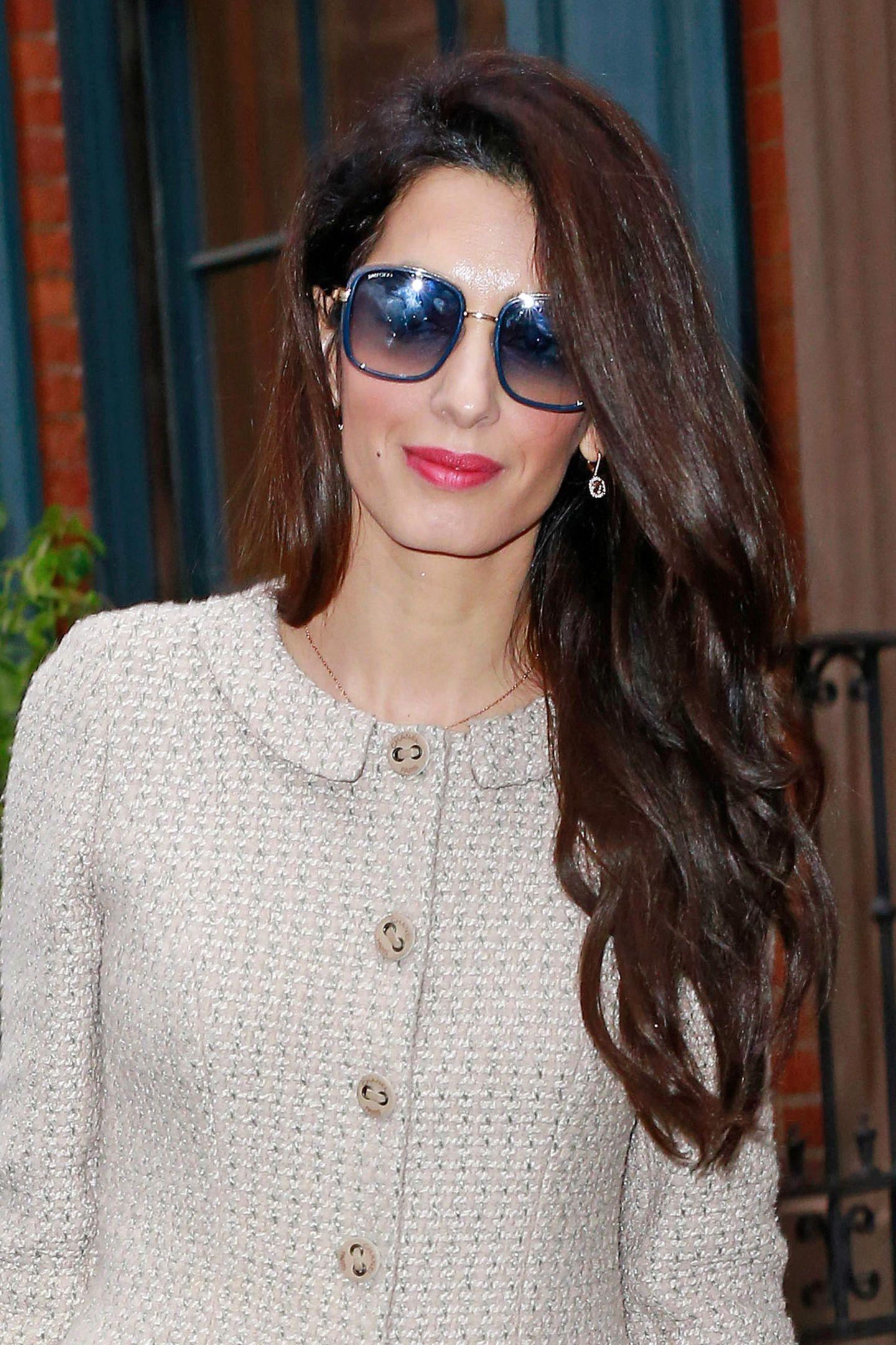 Auf den Knöpfen ist das Label des eleganten Second-Hand-Zweiteilers zu lesen: Chanel Paris. Passend dazu trägt Amal eine Sonnenbrille im dezenten Retro-Look und sicher nicht ganz günstige Diamant-Ohrringe.