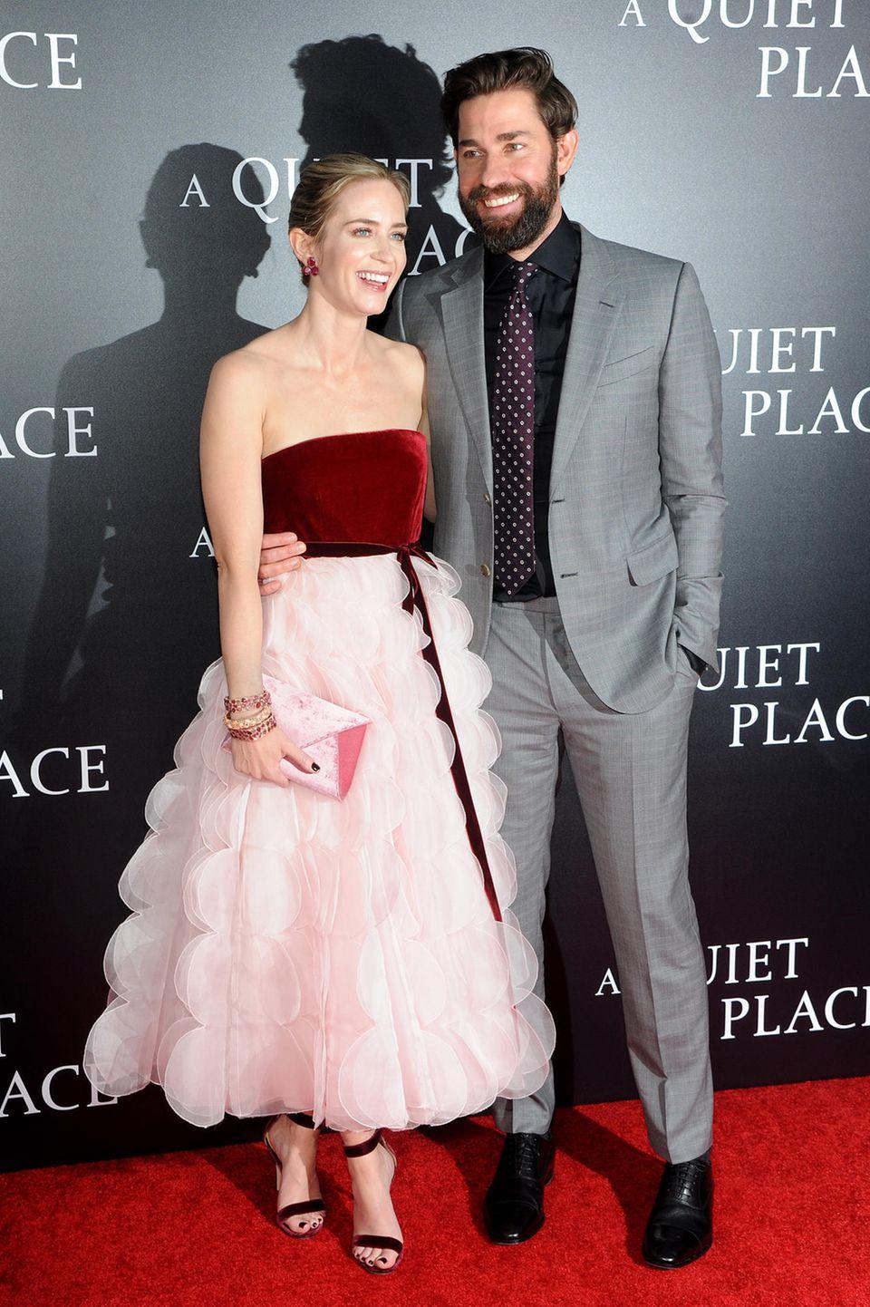 """Emily Blunt und John Krasinki sind wirklich ein Vorzeige-Paar, erst recht auf dem roten tepich. Bei der Premiere von """"A Quiet Place"""" in New York bezaubert sie im verspielten Samt-und Tüll-Kleid von Oscar de la Renta, während in grauem Anzug dezent seine Frau strahlen lässt."""