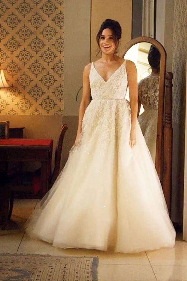 """In der Serie """"Suits"""" schlüpft Meghan Markle in ihrer Rolle als Rachel Zane in ein Brautkleid von Designerin Anne Barge. Es überzeugt durch einen V-Ausschnitt mit feinen Trägern, einen taillierten Schnitt und aufwendige Stickereien auf Tüll. Eigentlich eine passende Kreation für eine angehende Prinzessin."""