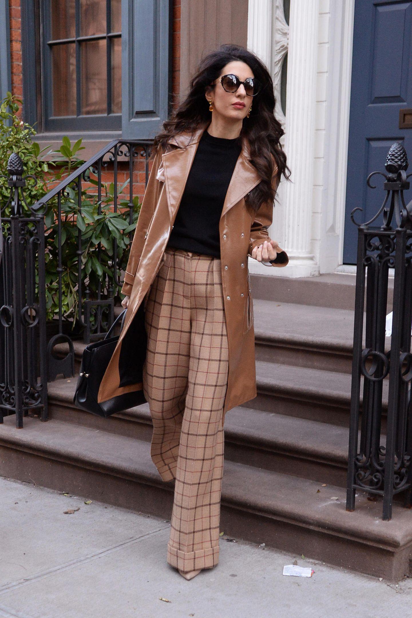 """In einer karierten Marlene-Hose und einem cognac-farbenen Ledermantel von Michael Kors verlässt Amal Clooney ihr Apartment in New York. Eine XL-Sonnenbrille und leichte Wellen im Haar verleihen ihr das gewisse, glamouröse Extra. In der Hand hält sie ihre """"Bar Bag"""" von Dior."""