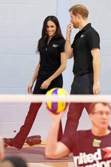 Unter dem Mantel zeigt sich Harrys Verlobte dann aber doch sportlich, und zwar im Polo-Shirt-Partnerlook mit ihrem Liebsten.