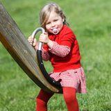 In einem karierten Kleid und farblich abgestimmten Pullover und Strumpfhose strahlt Celeste Trussardi auf dem Spielplatz. Auch wenn die Outfits der beiden Schwestern an diesem Tag sehr unterschiedlich sind, so tragen sie beide dieselben Schuhe.