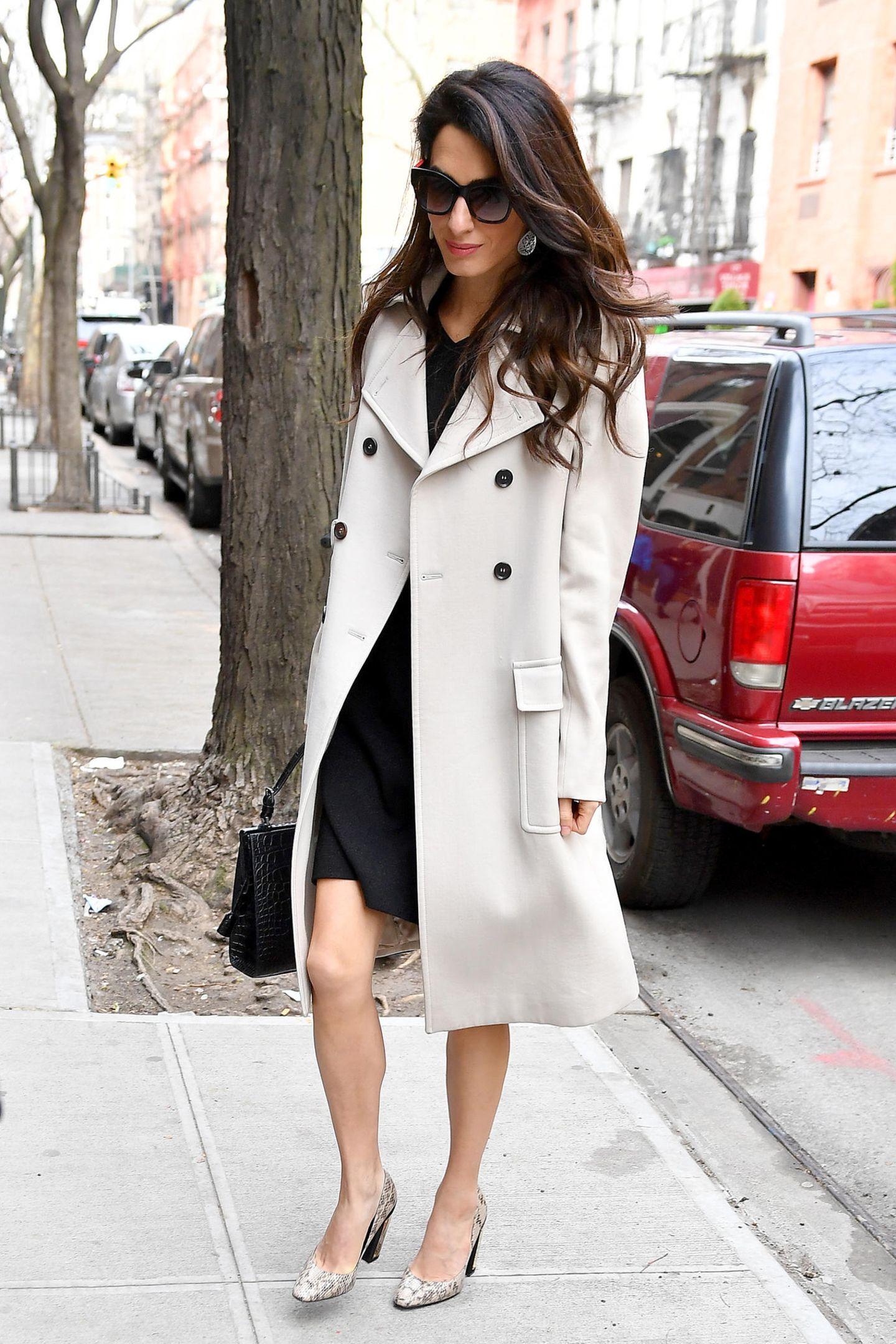 """Ein neuer Tag, ein neuer Look: Amal Clooney trägt einen cremefarbenen Trenchcoat über einem schwarzen Kleid und kombiniert dazu Schlangenlederpumps. In der Hand hält sie die """"Simone""""-Tasche von Michael Kors aus Alligatorleder in Schwarz."""