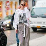 Das kurze Röckchen und die Lederstiefel tauscht Gigi zurück in New York gegen Chino-Hose und Sweatshirt ein. An die Liebe scheint sie dennoch weiterhin zu glauben; auf ihrem weißen Shirt ist ein Aufdruck ihrer sich küssenden Modelkolleginnen Cara Delevingne und Adwoa Aboah.