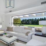 Der Wohnbereich mit Panoramablick ins Grüne verspricht herrlich entspannte Stunden. Auch hier dominieren klare Weißtöne den Raum. Hochwertige Ledersessel laden zu einer gemütlichen Lesestunde ein.