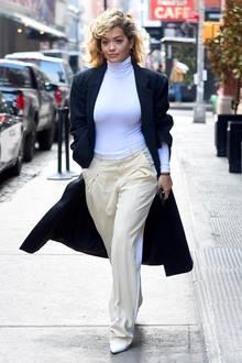 Einfach lässig! Rita Ora macht vor, wie einfach lässige Eleganz aussehen kann. Dunkler Mantel zum weißen Rollkragen-Shirt und cremefarbener Anzughose reichen da völlig aus.
