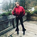Ihre schwarze Jeans bezirzt durch besondere Volant-Details am Bein. Dazu kombiniert sie schwarze Ankle Boots und einen XL-Strickpulli in Rot.