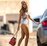 Sonnenbrille, Haarband und Korbtasche pimpen das Bikini-Outfit von Rachel McCord zum super Festival-Look auf.