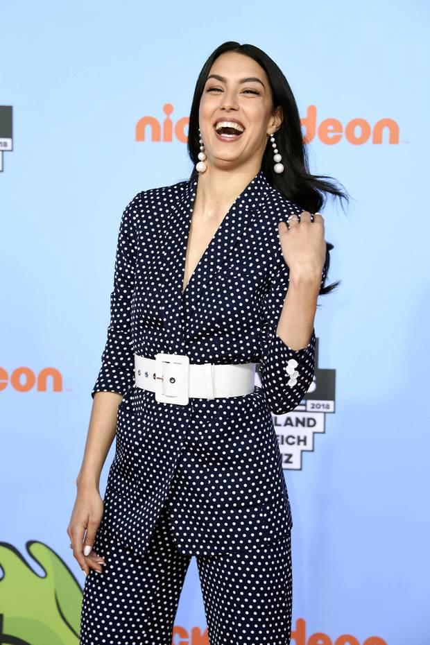 Dieser Look ist eine echte Punktladung! Zu den Kids' Choice Awards trägt Model und Moderatorin Rebecca Mir einen dunkelblauen Hosenanzug mit weißen Punkten. Dazu kombiniert sie einen weißen Gürtel und zauberhafte Perlen-Ohrringe.