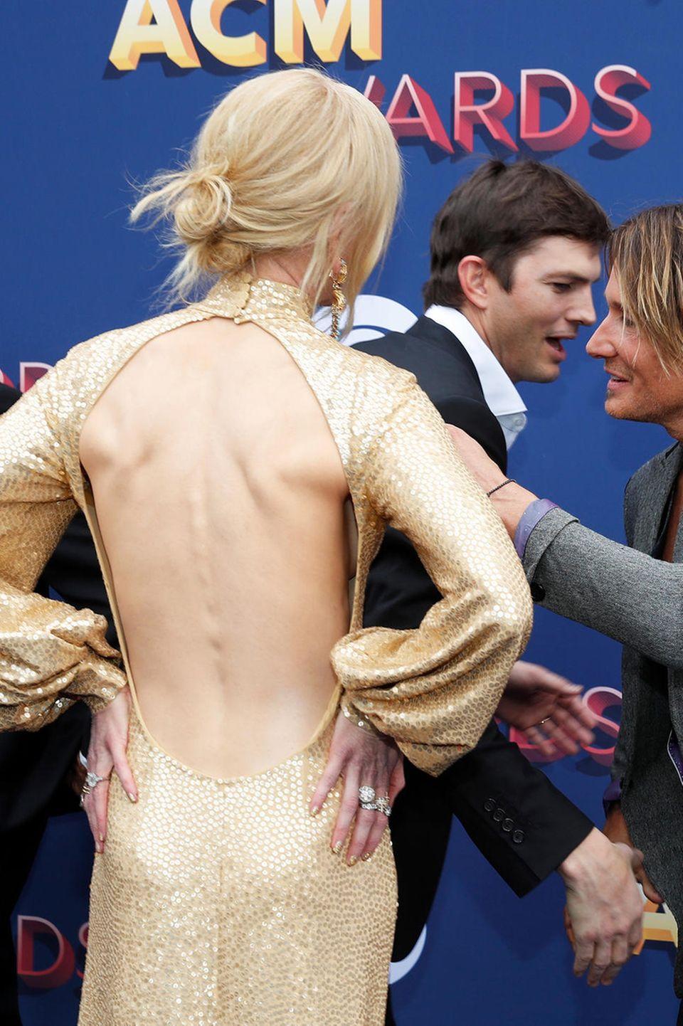 Die Rückenansicht von Nicoles Kleid ist besonders reizvoll, dabei könnte man glatt übersehen, dass mit Sam Eliott (l.) und Ashton Kutcher gerade noch zwei Hollywood-Stars über den roten Teppich der ACM Awards huschen.
