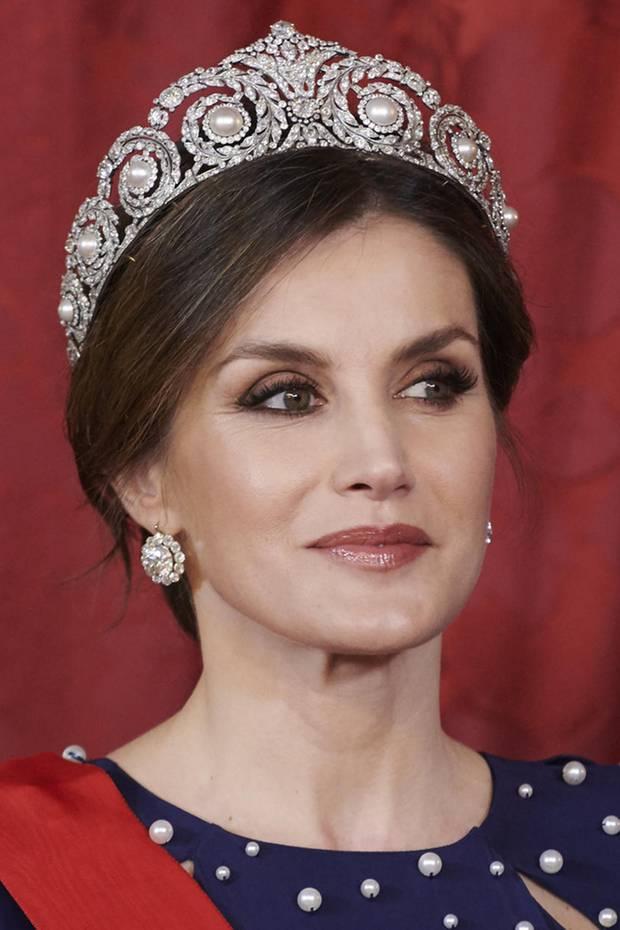 Letizia ist nicht die erste Königin, die dieses wundervolle Perlen-Diadem von Cartier trägt. Victoria Eugenie ist vor fast 100 Jahren die erste spanische Monarchin, die das funkelnde Schmuckstück ausführt. Im Laufe der Zeit verschwindet es allerdings aus dem Familienbesitz, findet den Weg jedoch zurück und landet...