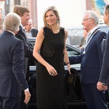 Königin Máxima kombiniert zu ihrem schwarzen, hübschen Kleid eine lange, schwarze Schlaghose. Ein Look, den man so heutzutage nun wirklich nicht mehr trägt.