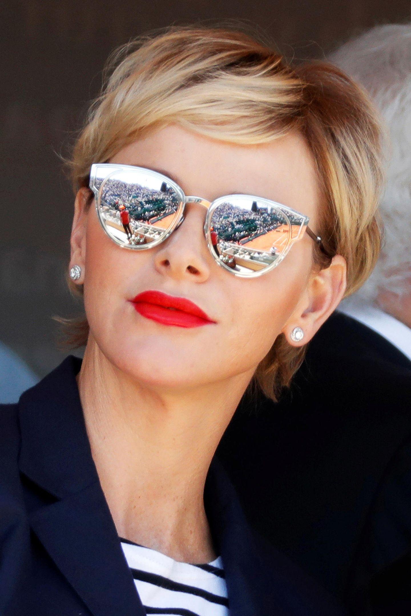 Nicht nur die komplett verspiegelte Sonnenbrille ist ein Hingucker auf der Tribüne, besonders Charlènes rote Lippen und ihr lockeres Haar-Styling fallen ins Auge.