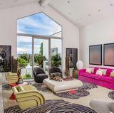 Eines der zahlreichen Wohnzimmer des Hauses ist recht farbenfroh gestaltet. Die pinke Couch, sowie die Teppiche im Animalprint sind wahre Hingucker.