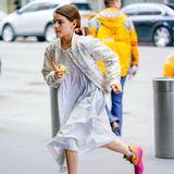 Huch, wo willst du denn hin? Suri Cruise rennt mit einem angebissenen Apfel durch die Straßen des Big Apple. Die 12-Jährige trägt ein sommerliches Kleid mit hellblauen Streifen, eine geblümte Bomberjacke und pink-braune Boots.