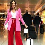 Was für ein cooler Look! Jana Ina Zarella setzt auf absolutes Colour-Blocking mit einer roten Schlaghose in Kombination mit einem pinkfarbenen Longblazer und zieht damit alle Blicke am Flughafen auf sich.