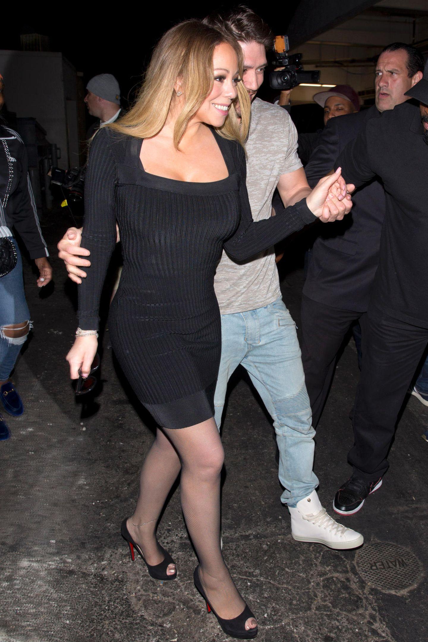 Wow! Im April 2018 zeigt sich Mariah nach einer angeblichen Magenbandoperation in Topform mit ihrem Freund Bryan Tanaka. Das enge schwarze Kleid betont ihre schmale Silhouette und die schwarzen Heels verlängern ihre schlanken Beine zusätzlich.