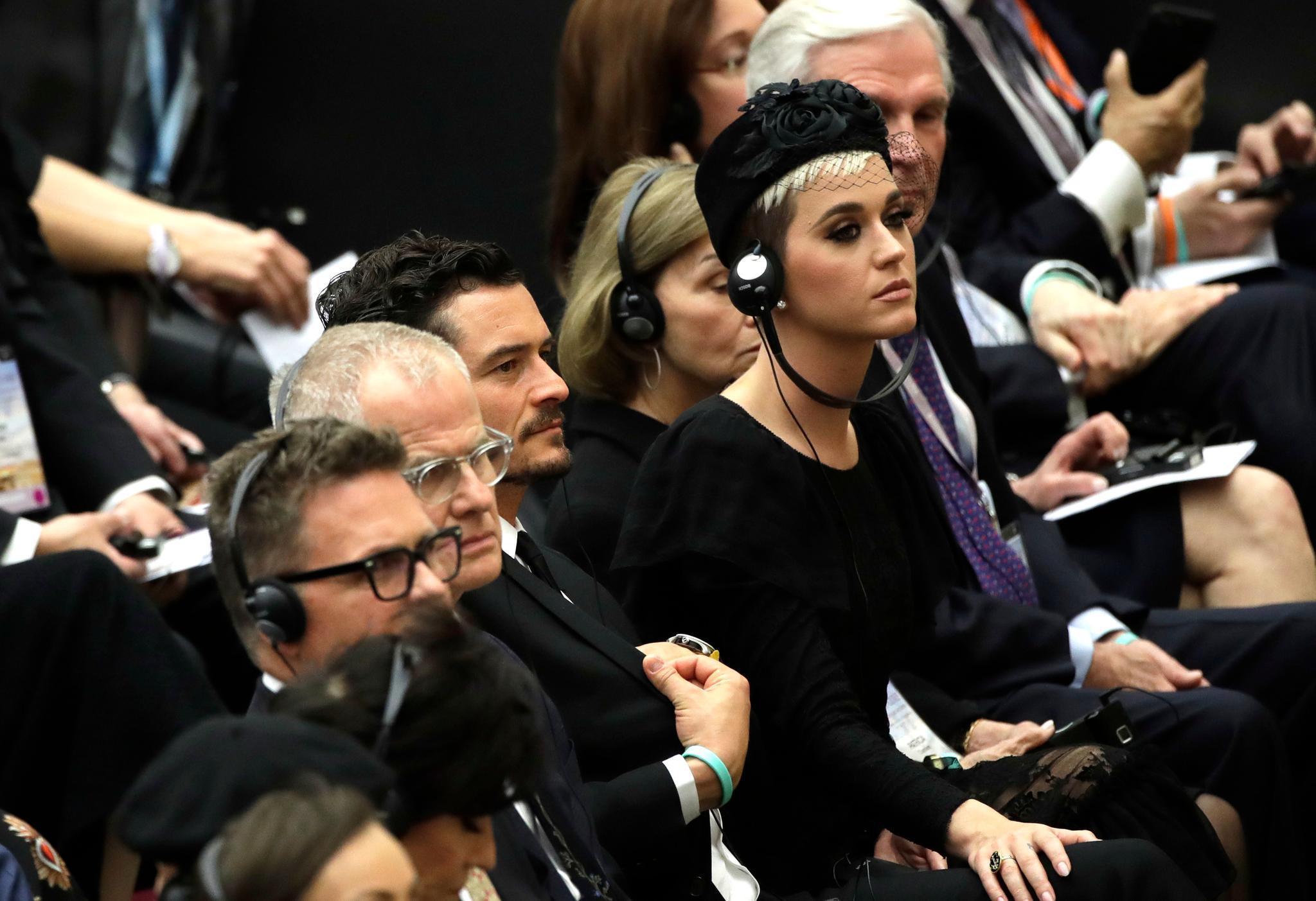 Während sie den Rednern lauschen, wandert die Hand von Katy Perry auf das Knie von Orlando Bloom, der neben ihr sitzt.