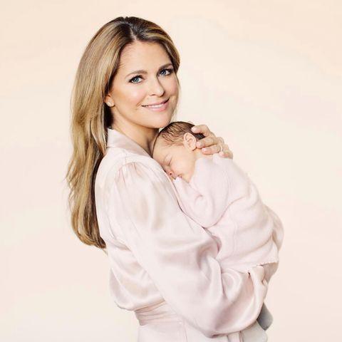 27. April 2018  Mamas ganzer Stolz: Prinzessin Madeleine posiert für die Fotografin in einer blassrosa Bluse. Tochter Prinzessin Adrienne schmiegt sich schlafend an Mamas Brust. Familienglück pur!