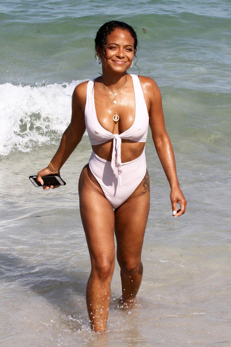 Mit strahlendem Lächeln und strahlend weißem Monokini entsteigt Christina Milian den Fluten am Miami Beach. Hoffentlich ist ihr Smartphone wasserdicht.