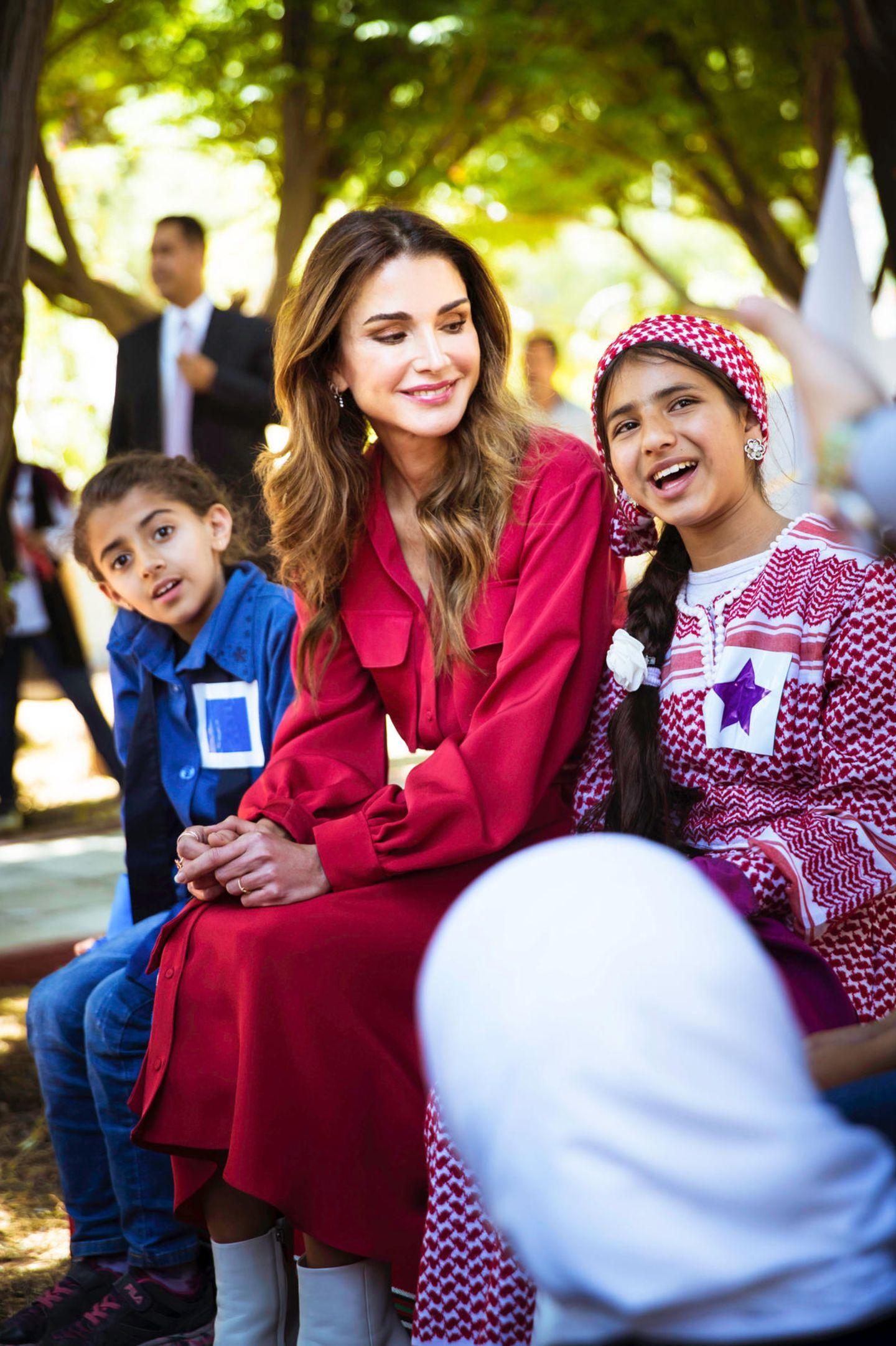 Königin Rania unterhält sich bei einem Volksfest im Millennium Park in Jordanien vergnügt mit jungen Besucherinnen.