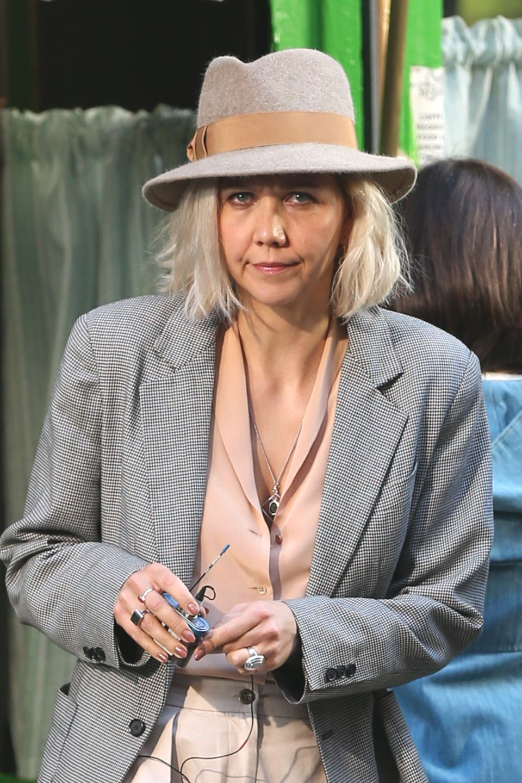 """SchauspielerinMaggie Gyllenhaal ist kaum wiederzuerkennen. Auf den neuesten Bildern vom Set der Serie """"The Deuce"""", die Maggie aktuell in New York dreht, schaut die Schauspielerin mit blondem Haar und grimmiger Miene in die Kamera."""