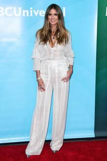 Ganz so unschuldig, wie das weiße Outfit scheint, ist es nicht: Der Zweiteiler von Heidi Klum ist leicht durchsichtig und hat glitzernde Streifenelemente. Auch der tiefe V-Ausschnitt ist sehr sexy und gibt dem eleganten Outfit das gewisse Extra. Besonderer Hingucker sind jedoch ihre Accessoires...