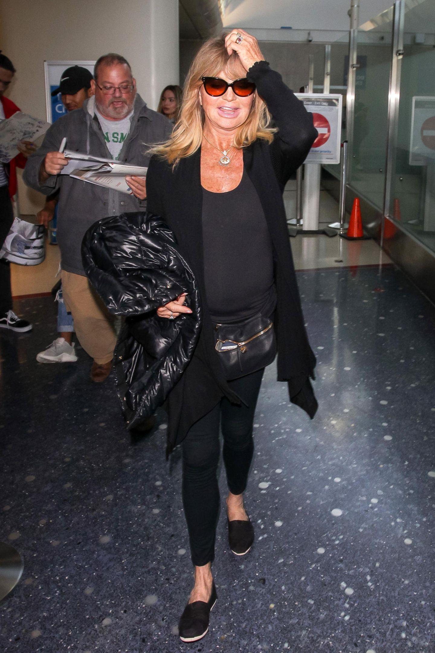 Ganz in Schwarz mit gemütlichen Espandrillos, praktischer Bauchtasche und einer warmen Jacke gegen kühle Kabinenluft zeigt sich Goldie Hawn am Flughafen von L.A.