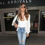 Abgeschnittene Jeans und und eine fransige weiße Lederjacke zu passenden Retro-Bootssind für Heidi Klum lässig genug für lange Flugreisen.