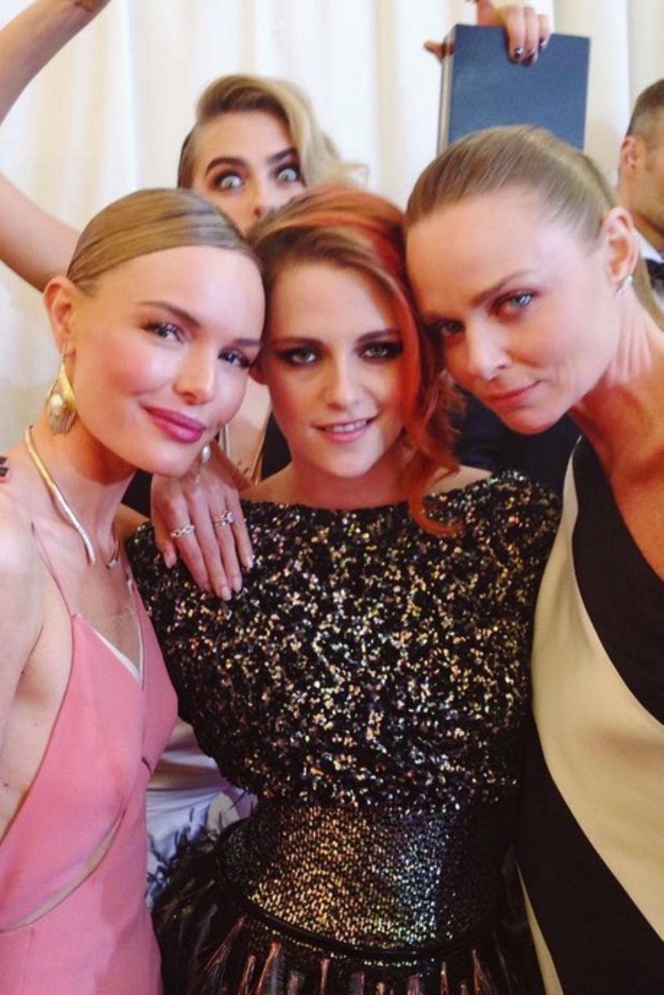 Kate Bosworth, Kristen Stewart und Stella McCartney posieren gemeinsam für ein Foto. Na, erkennen Sie, werdas schöne Gruppenbild im Hintergrund sprengt? Richtig, es ist das Model Cara Delevingne, die ganz aufgeregt im Hintergrund springt.