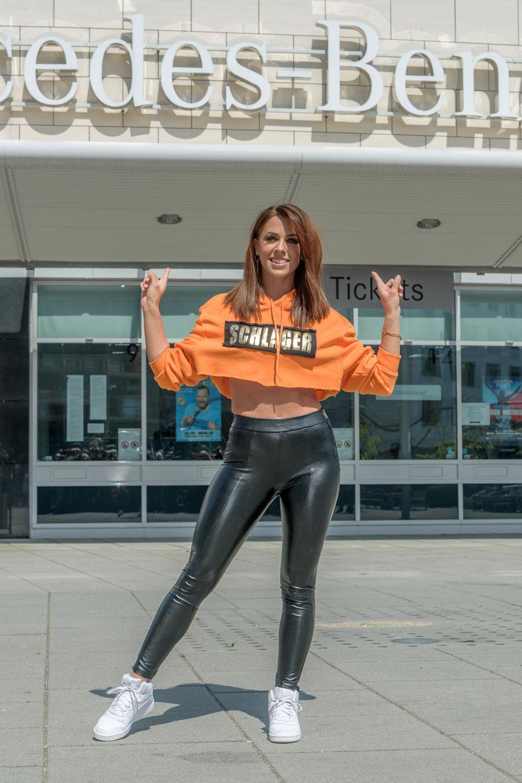 """Sie ist endlich zurück - und in Topform: Vanessa Mai posiert vor der Berliner """"Mercedes Benz""""-Arena, wo sie ihre neue Tour präsentiert. In einer engen Lederleggins und mit einem orangen Hoodie, der gerade so ihre Brust bedeckt zeigt sie, dass sie nach ihrem Sturz vor einigen Tagen endlich wieder fit zu sein scheint."""