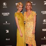 Luisa Hartema und Monica Ivancan entscheiden sich beide für sommerliche Gelbtöne. Während Luisa ein bodenlanges Seidenkleid mit hochgeschlossener Front trägt, wählt Monica ein geblümtes Kleid mit Volants und tiefem V-Ausschnitt.