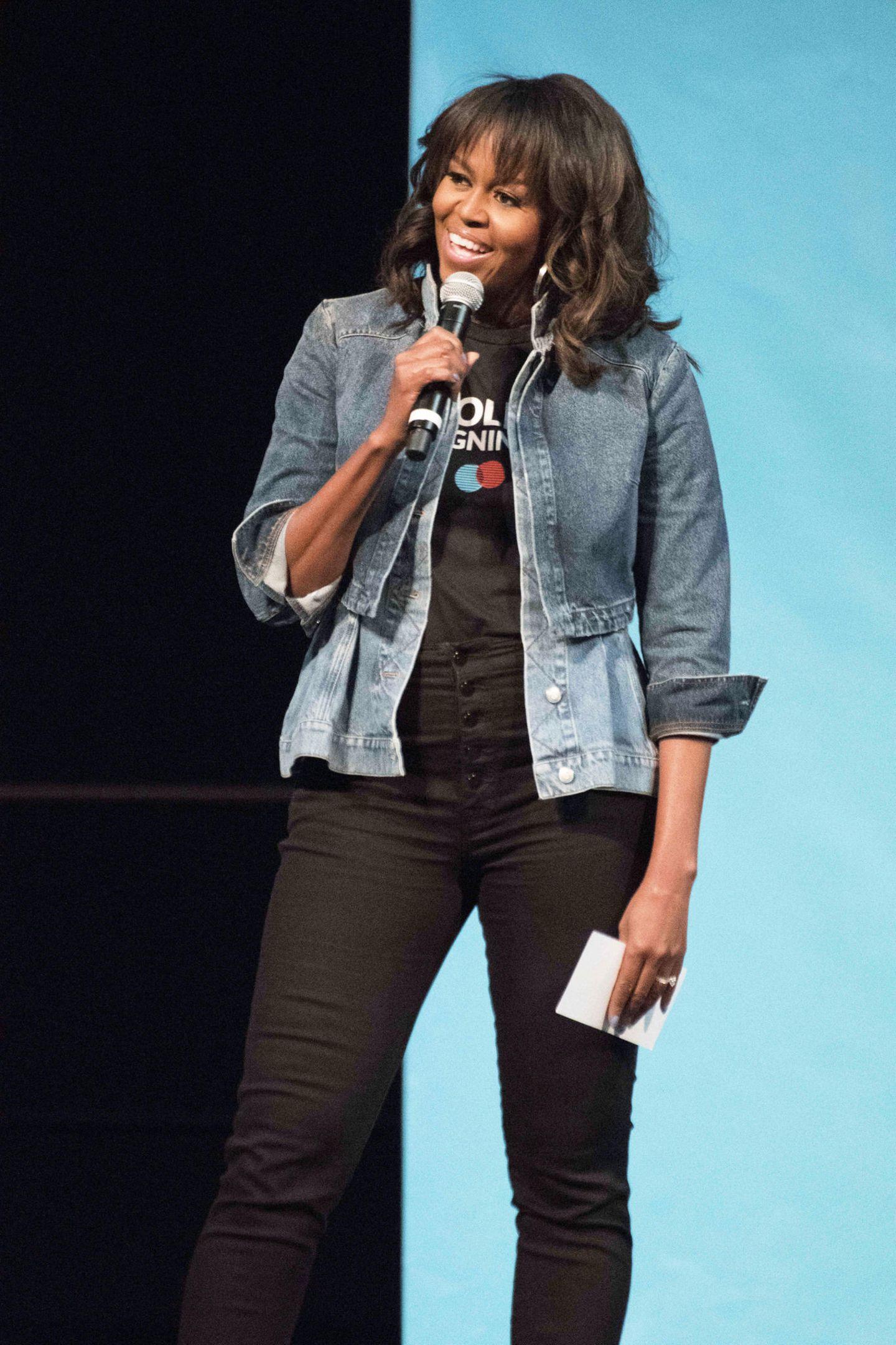 Lange haben wir die ehemalige First Lady Michelle Obama nicht mehr gesehen. Nun zeigt sie sich beim College Signing Day in Pennsylvania und überrascht in einem ungewohnt lässigen Look. Michelle erscheint in einer schwarzen High-Waist-Hose, T-Shirt und Jeansjacke. Ihr Haar trägt sie offen, gelockt und mit Pony.
