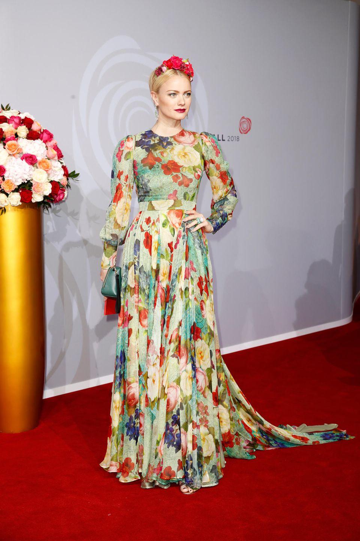 Model Franziska Knuppe wählte den perfekten Lookfür den Abend: Ein bodenlanges, buntes Kleid mit Rosen-Print von Eva Poleschinski für den Rosenball. Dazu kombiniert sie eine Handtasche von Aigner und einen tollen Blumenkranz als Haarschmuck.