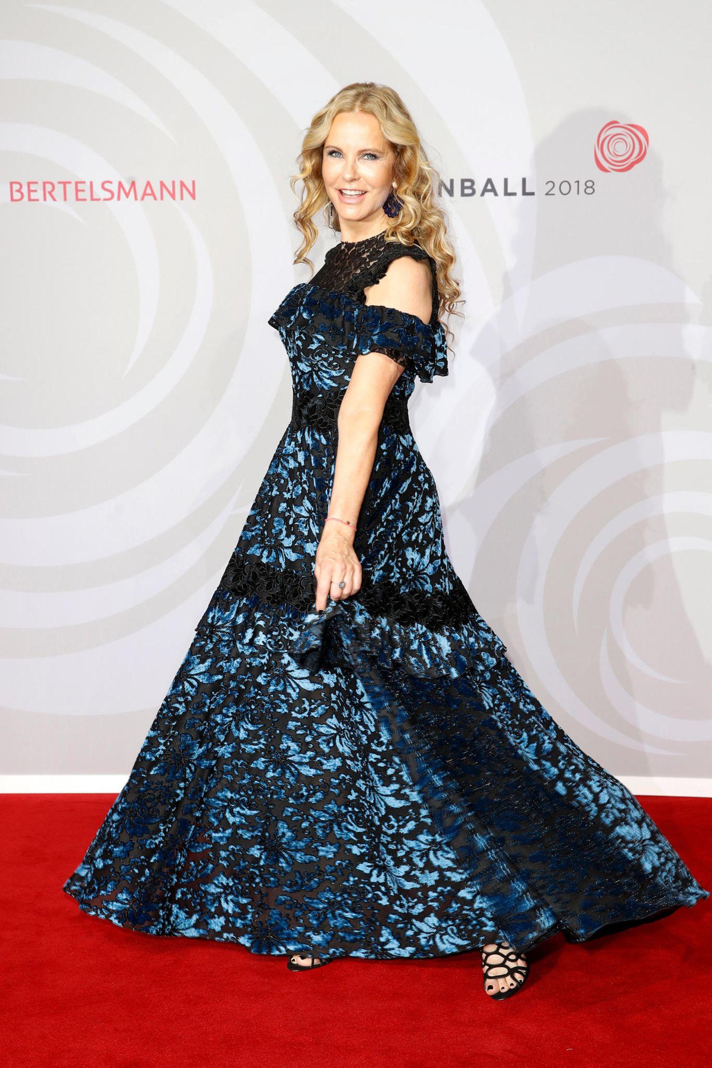 Moderatorin Katja Burkard schwebtein einem bodenlangen Blumenkleid mit Spitzen-Details über den Red Carpet.