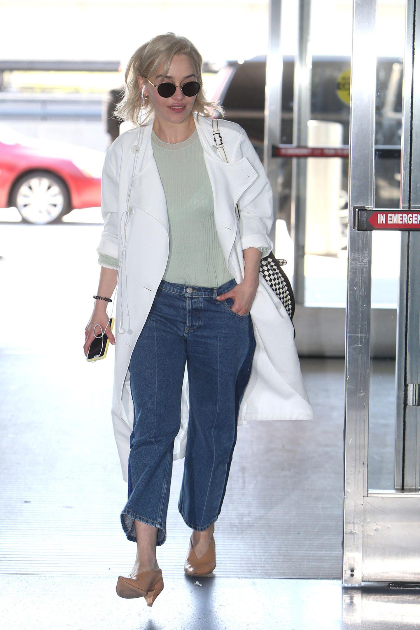 """Entspannt schlendert """"Game of Thrones""""-Star Emilia Clarke amNew Yorker Flughafen entlang. In weiter Jeans und bequemem Pulli lässt es sich doch super fliegen! Ach ja, die obligatorische Sonnenbrille darf natürlich auch nicht fehlen."""