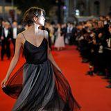 Ein flüchtiger Blick über die Schulter verzaubert die Gäste vor dem roten Teppich: Leichtfüßig schwebt die russische Schauspielerin Anna Chipovskayadurchs Blitzgewitter.