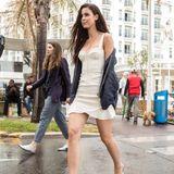Neuer Tag, neuer Look: Während ihrer Zeit in der französischen Filmhauptstadt scheint Lena mit verschiedenen Looks experimentieren zu wollen. Zu einem weißen Kleid in Korsagenoptik kombiniert sie eine coole Bomberjacke und durchsichtige Slip-On-Heels.