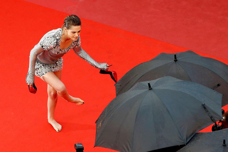 Hollywoodstar Kristen Stewart, Mitglied derJurybei den Filmfestspielen, scheint die hohen Absätze leid zu sein und zieht ihre Pumps mitten auf dem roten Teppich aus.