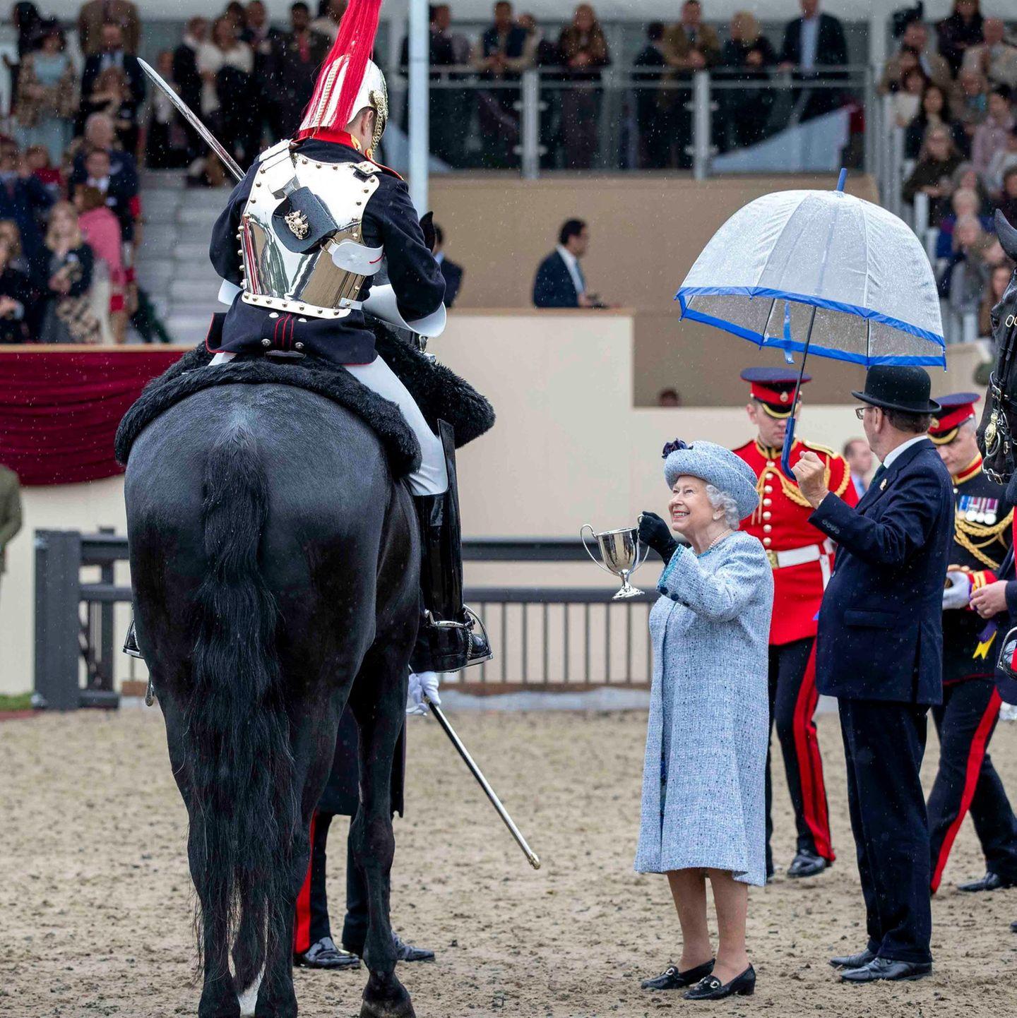 """12. Mai 2018  Die Queen hat den Freizeitlook mit Kopftuch gegen ein offzielleres Outfit mit Hut getauscht und waltet ihres Amtes bei der """"Royal Windsor Horse Show"""". Ein Mitarbeiter hält schützend einen Schirm über die 92-Jährige, die aber wohl eher eine Leiter bräuchte, um den Pokal zu überreichen."""