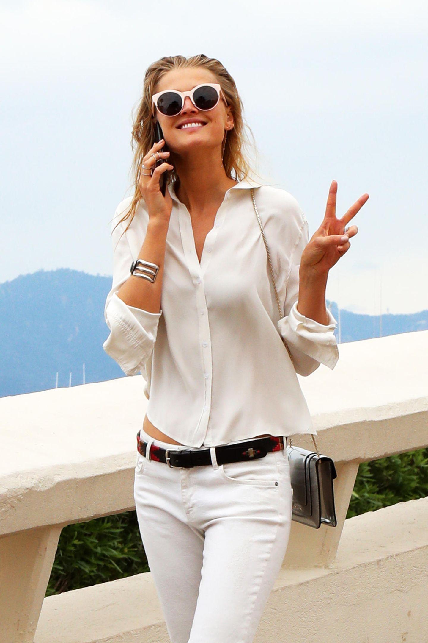 Zu Toni Garrns lässigem Jeans- und Blusen-Look in Weiß passt die süße Sonnenbrille mit rosafarbenen Gestell perfekt.