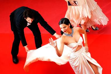 Supermodel Adriana Lima winkt entspannt den Besuchern zu, während der fleißigeAssistent mit ihrer wallenden Schleppe zu kämpfen hat.