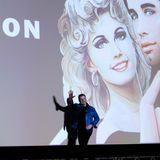 """Hollywoodstar John Travolta winkt den Zuschauern zu. Am Strand von Cannes wird sein Klassiker """"Grease"""" aufgeführt. Mehr als genug Grund zum Anlass gibt es, schließlich ist der Kultfilm 40 Jahre alt geworden."""