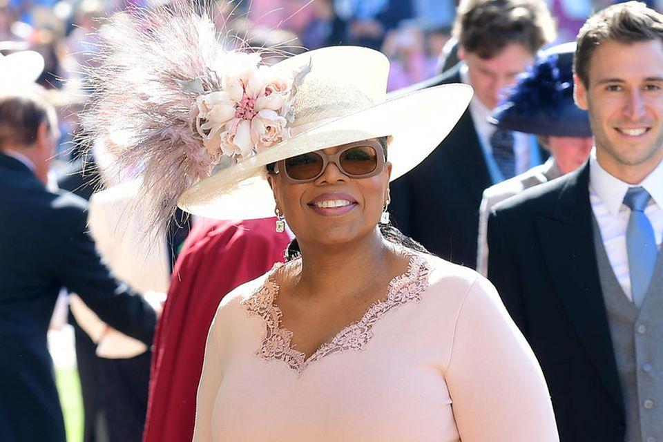 """Oprah Winfrey zieht alle Blicke auf ihren Hut, der mit Federn """"erneuert"""" wurde."""