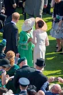 Küsschen mit Hut will gelernt sein: Herzogin Meghan und Herzogin Camilla manövrieren um ihre Kopfbedeckungen herum.