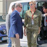 """In einem stylischen, khakifarbenen Overall präsentiert Fürstin Charlène ihre Kurven an der """"Grand Prix""""-Rennstrecke in Monaco. Dazu trägt sie schwindelerregend hohe Plateau-Heels, die ihren Mann, Fürst Albert, klein neben ihr aussehen lassen."""