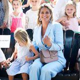 Madeleine trägt einen hellblauen Hosenanzug mit zweireihigem Jackett aus Leinen. Die Kombination stammt von Massimo Dutti und ist eine Limited Edition für knapp 300 Euro. Dazu kombiniert die Prinzessin eine Valentino-Tasche für knapp 1.700 Euro, die sie schon häufiger getragen hat.