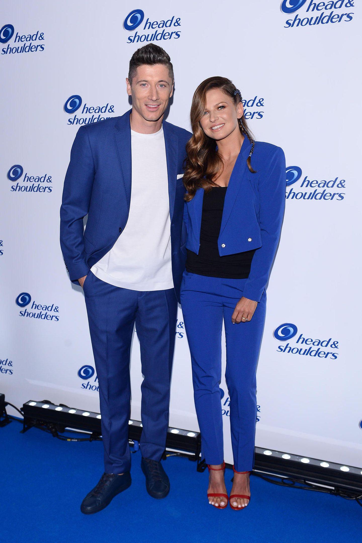 Robert Lewandowski und seine Anna posieren in farblich abgestimmten Outfits auf dem blauen Teppich eines Events in Warschau. Während er seinen blauen Anzug nur mit einem schlichten weißen Shirt kombiniert, peppt sie ihren Zweiteiler mit einem schwarzen Top und roten Riemchen-Heels auf.